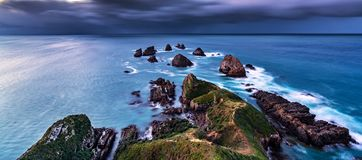 The end of land and the start of sea. The reef group near the Nugget Point lighthouse, let me remember that `Here, where the land ends and the sea begins royalty free stock images