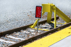 End of the Line. A red warning indicator and yellow barrier at the end of railroad tracks Stock Photo