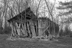 The end of the line for an old barn. An aging wooden barn in a rural area on it`s last legs stock image
