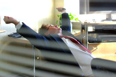 The End of a Long Day. Businessman stretching, seen thru an interior window Stock Photos