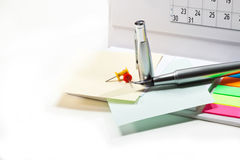 End of the month summarizing the work done. Desk calendar, pen, pieces of paper on white background Royalty Free Stock Photo