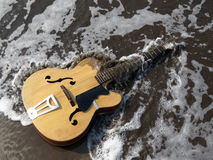 End of a Musical Era. A metaphorical image of an old guitar being washed away by sea waves depicting the end or death of an era of music leaving a legacy behind Royalty Free Stock Photo