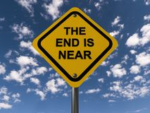 The end is near. On yellow roadway caution sign against blue skies with clouds royalty free stock photography