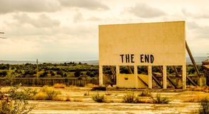 The End !. An old cinema billboard has the deep words of 'The End' painted onto a blank board, in a degraded parking lot stock photo