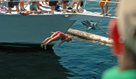 End Over... End. Girl doing a back flip off the bow of a boat Royalty Free Stock Photography