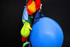 Some burst, deflated balloons and one inflated balloon hanging o. End of a party. Some burst, deflated balloons and one inflated balloon hanging on threads Royalty Free Stock Photo
