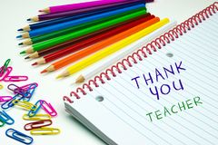 Thank you Teacher for end of school year. End of primary school year concept to give thanks to the teachers. Colored pencils, paper clips and open book with Stock Photos