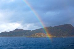 End of rainbow over an island Stock Photos