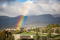 End of a rainbow in the sky over the city in sunny day royalty free stock photo