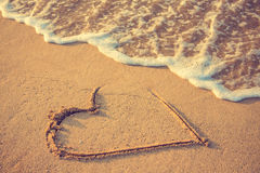 End of relationship. Heart drawn on the beach sand being washed away by the waves of the sea. Love affair, summer love or breakup and divorce concept. Ephemeral Stock Photos
