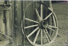 End of the road. Old wagon wheel with broken spokes, resting against the side of a barn stock photo