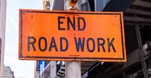 End Road Work. Warning sign, orange color, blur buildings background. End Road Work. Road construction works end, Warning sign, orange color, blur New York city stock photography