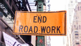 End Road Work. Warning sign, orange color, blur buildings background. End Road Work. Road construction works end, Warning sign, orange color, blur New York city royalty free stock images