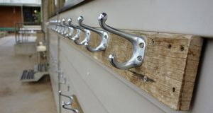 Row Of Bag Hooks At School. A row of bag hooks on the outside of a classroom have been relieved of a heavy load at the end of the school day Royalty Free Stock Photography