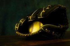 End of the Season. Baseball in ball glove laying on wood surface. End of baseball season. Baseball glove, Baseball. Black Leather stitching. Stitching. Baseball Royalty Free Stock Image