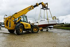 End of season. Lifting a yacht onto a trailer using a JCB at Brancaster Staithe ready to go into winter quarters. Very much end of season now the northerly Royalty Free Stock Images