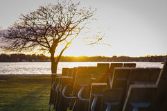 End of Season. Tables put away for the season take in a sunset by the lake Stock Photos