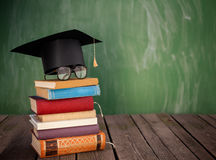 After the end of shool. Graduation cap with reading glasses on top of the books Royalty Free Stock Photo