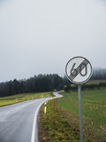 End of speed limit with curvy road. Sign indicating end of speed limit with curvy road in Germany Royalty Free Stock Photo