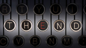 The End of The Story. Close up of old manual typewriter keyboard with scratched chrome keys that spell out THE END. Both words share the letter, 'E', highlighted Royalty Free Stock Photo