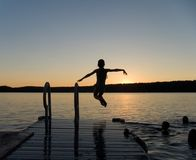 End of summer. Girl jumping off a pier at dusk stock images