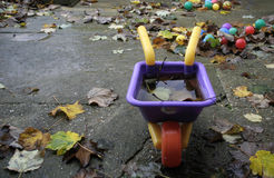 The End of the Summer. A child's wheelbarrow left out in the autumn, filled with rainwatr and falling leaves Royalty Free Stock Photo
