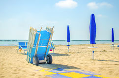 End of summer beach deckchair closed umbrella Stock Photos