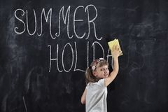 End of summer holidays. Schoolgirl standing in front of a chalkboard and wiping summer holidays inscription from it with a sponge. End of summer holidays and royalty free stock photography