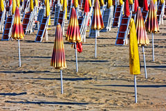 End of summer - Parasols and sun loungers closed on the beach Stock Image