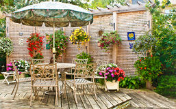 End of Summer on Patio. Patio in the early Fall, showing a table with umbrella, chairs, flower boxes, privacy fence, and green bushes Stock Photos