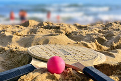 End of summer. Two rackets and ball on the sand beach Stock Photo