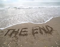 THE END text written on the sand and the wave that is deleting t. THE END text on the sand and the wave that is deleting the word can be used for the end of Royalty Free Stock Images