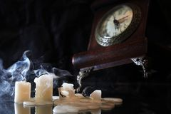 End Of Time. Set of extinguished candles near old clock on nice dark background royalty free stock photo