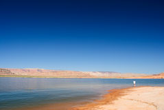 The end to nowhere. Single person standing alone in a vast barren landcape near a lake Stock Photography