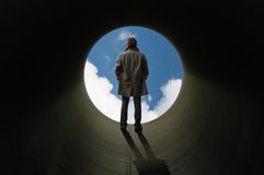 At The End of Tube. There is no other way out. Man stands silhouetted at the end of tube before a bright sky Royalty Free Stock Photo