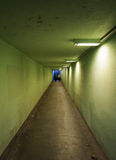 At the end of the tunnel. Two girls walking inside a green illuminated tunnel Royalty Free Stock Photos