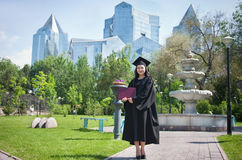 End of University. The girl the graduate of university with the diploma in hands, in park Stock Photography
