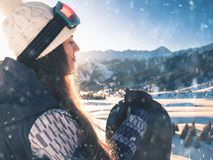 End of winter season. Portrait of snowboarder girl on the background of high mountain stock photos