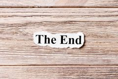 The End of the word on paper. concept. Words of The End on a wooden background.  royalty free stock images