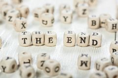 The End word written on wood block. Word THE END formed by wood alphabet blocks. On old wooden table Royalty Free Stock Photos