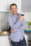 At the end of work: single man drinking glass of wine in the kit Royalty Free Stock Photos
