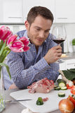 At the end of work: single man drinking glass of wine in the kit Royalty Free Stock Image