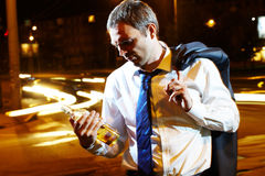 End of workday. Portrait of a businessman with a bottle of whisky at night Royalty Free Stock Photos