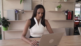 The end of the working day successful employee looking at the camera. The end of the worBusiness woman typing on the laptop. Mixed race female in the modern stock video footage