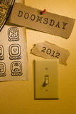 End of the World. Old papers with the words Doomsday and 2012 and a Mayan calendar next to a light switch representing the end of the world Stock Image