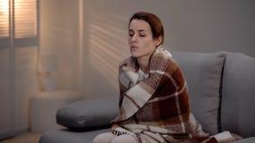 Am Ende deprimierte junge Dame des Kranken bedeckt mit dem Plaid, das allein im Pflegeheim sitzt lizenzfreie stockbilder