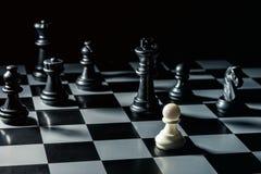 Ende des Spielcheckgehilfen, einfarbiges Schwarzweiss mit Höhepunkt Weißer Kontrolleur bedroht den schwarzen Schachgegner stockfoto