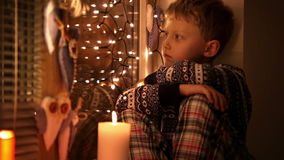 Ende des Weihnachtskleinen traurigen Jungen, der auf dem Fensterbrett sitzt stock video