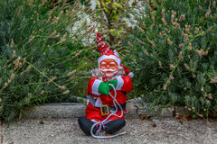 An endearing Santa Claus sitting in the middle of the garden. Of a village house Stock Photo