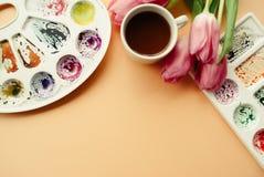 Endecha creativa del plano de la taza de café, paletas de la acuarela y ramo de tulipanes rosados Lugar de trabajo del artista en Foto de archivo